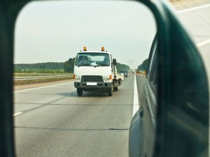 Tow truck approaching in side vehicle mirror