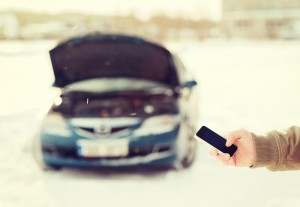Man holding phone in front of car broken down in snow