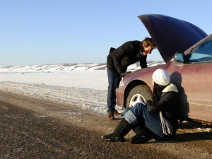 Couple stranded on side of road with broken down car